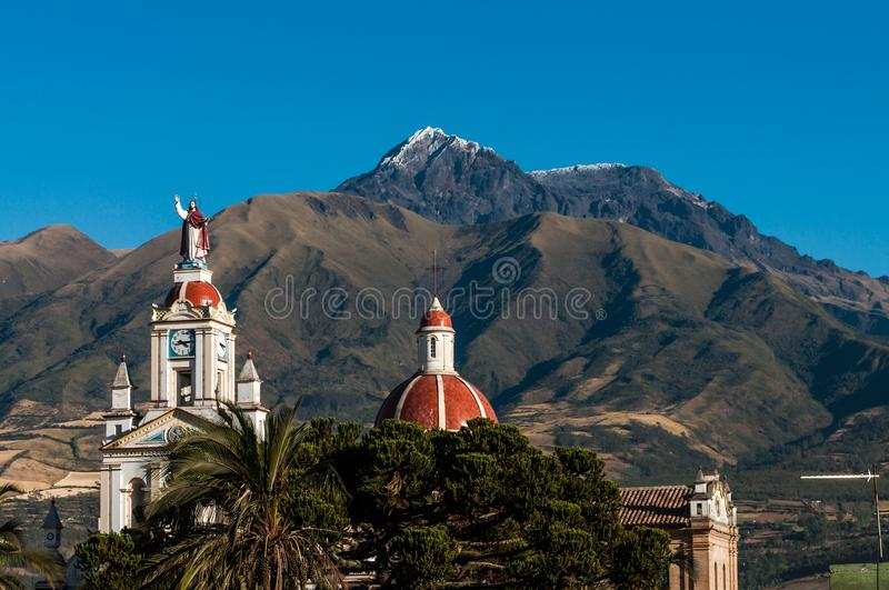 Sunlight on cotacachi`s church and the volcano with hard-focus in the background. Sunny day in cotacachi village, equator and the volcano with the same name in stock images