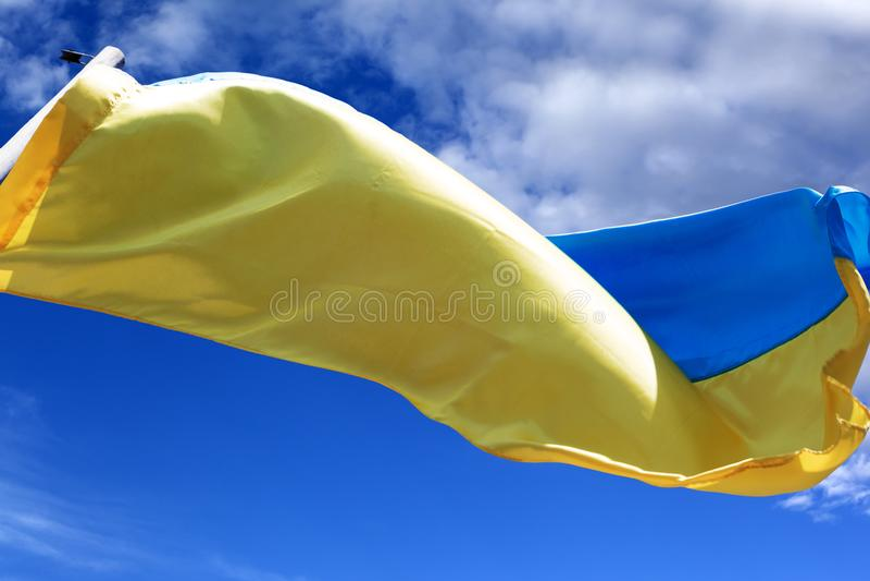 Sunlight flag of Ukraine waving in wind on blue sky stock image