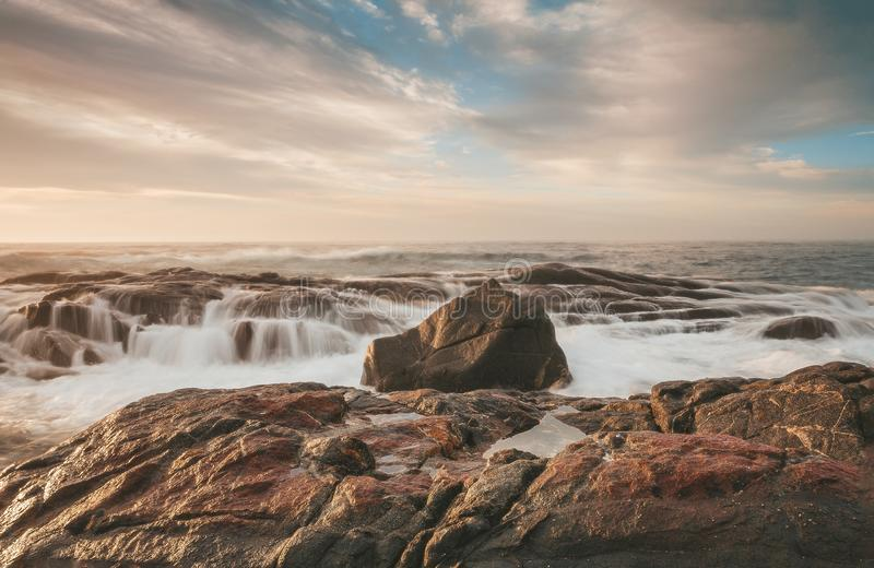 Sunlight on coastal rocks with ocean waterfall cascades. Sunlight filtered through cloud hitting coastal rocks that become coastal waterfall cascades with the stock image