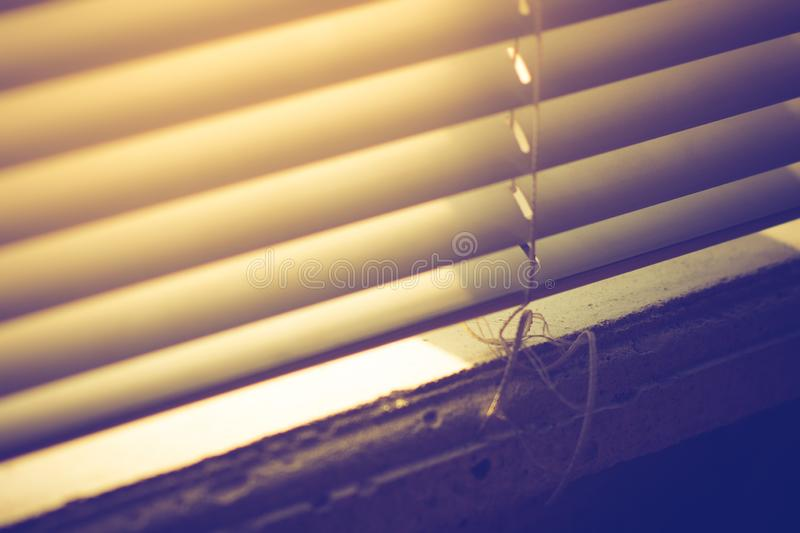 Sunlight through horizontal closed blinds. Sill in the right corner royalty free stock photos