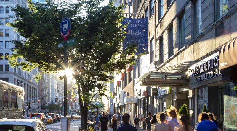 Sunlight shines on busy crowds of people walking down the sidewalk on 23rd Street through New York City royalty free stock photo