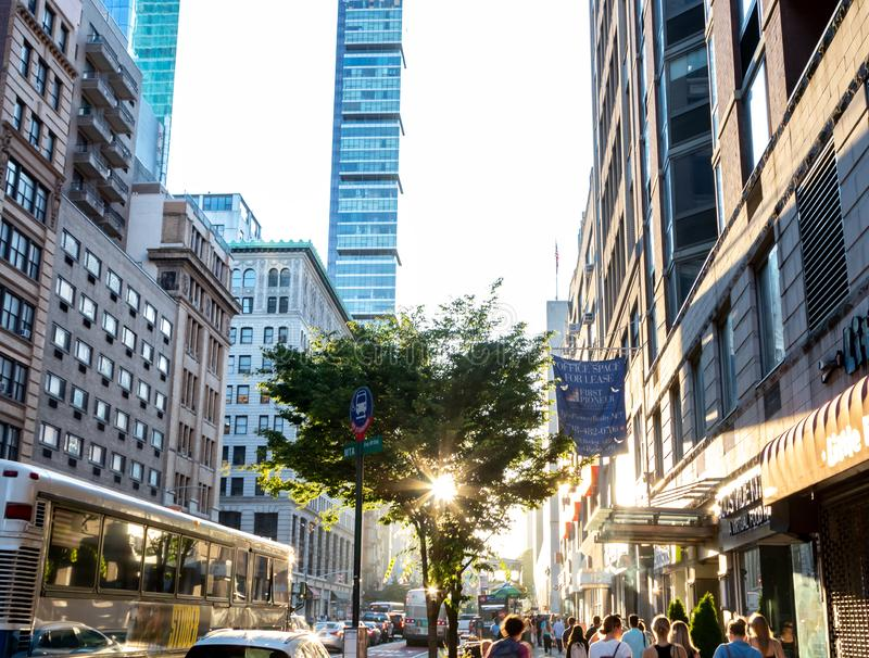 Sunlight shines on busy crowds of people walking down the sidewalk on 23rd Street through New York City royalty free stock images