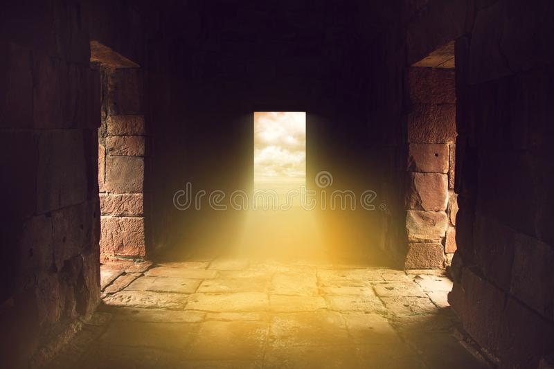 Sunlight shines through the door in the end of ancient stone temple stock photography