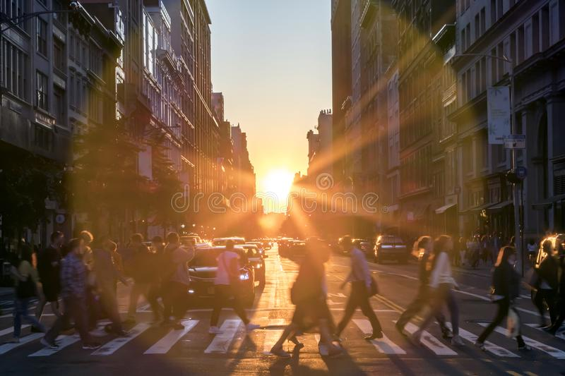 Sunlight shines over the buildings and people in New York City royalty free stock images
