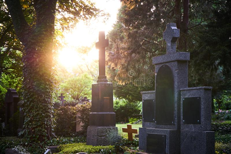 Sunlight shines through the trees of a graveyard touching old tombstones on a graveyard at sunset in the evening stock photos