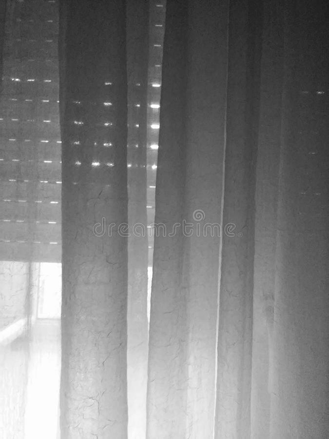 Black and white blinders and see-through curtain. Sunlight shining through blinders and a see-through curtain. black and white royalty free stock photo