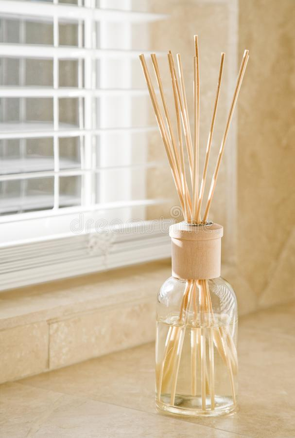 Sunlight shining through window blinds onto fragrance diffuser on stone tile bathroom counter. Clean, bright, fresh house home royalty free stock photo