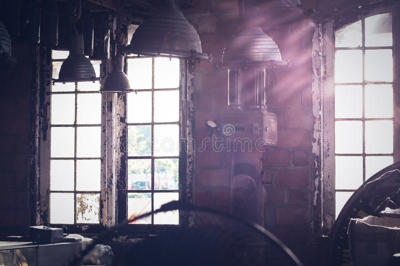 Sunlight shining through the windows of an old abandoned industrial warehouse building. Vintage loft idea background stock photography
