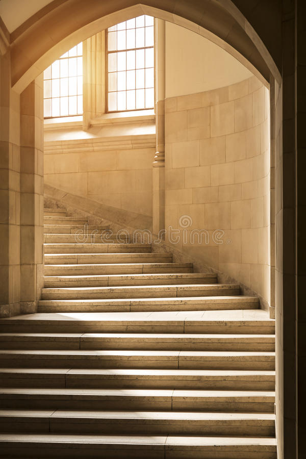 Sunlight shining through windows onto a classic, gothic style stone stairway curving upward through an archway. Bright sunlight shining through windows into royalty free stock photography