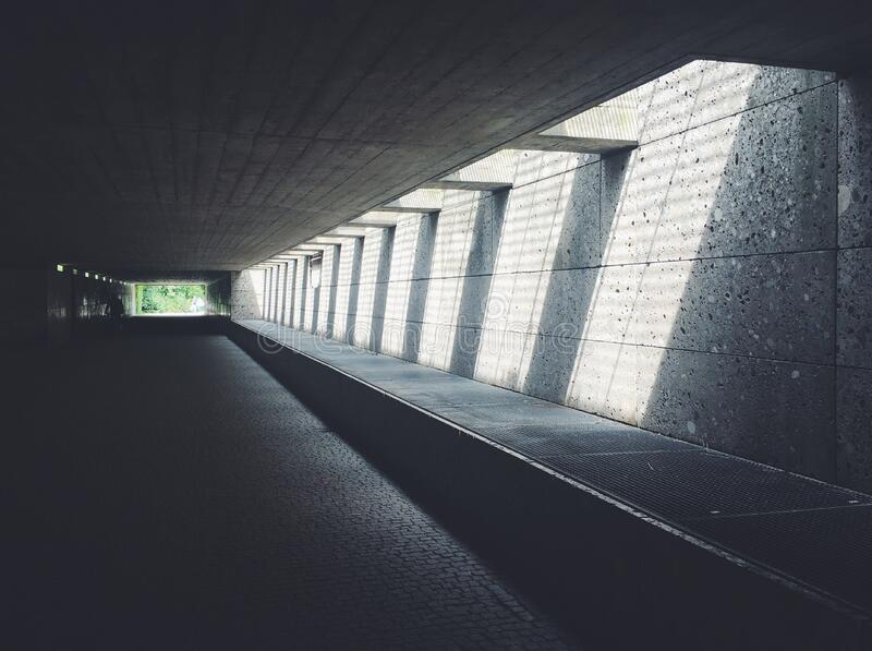 Sunlight Streaming Through Concrete Opening of Underground Passageway royalty free stock image