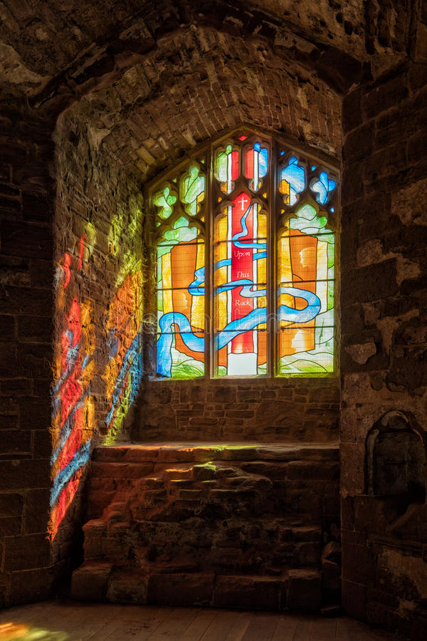 Sunlight streaming through a stained glass window, Goodrich Castle, Herefordshire. Mid-morning sunlight streaming through the stained glass window above what royalty free stock photography