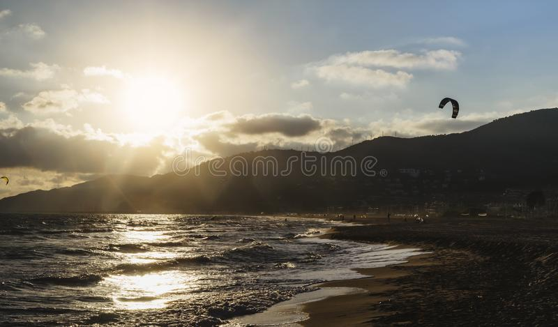 Sunlight sunset on horizon ocean on background seascape atmosphere rays sunrise. Relax view waves sea with kitesurfing on sand. Beach, sun light flare nature royalty free stock photos