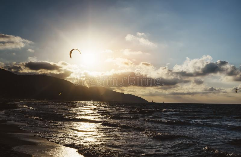 Sunlight sunset on horizon ocean on background seascape atmosphere rays sunrise. Relax view waves sea with kitesurfing on sand. Beach, sun light flare nature stock image