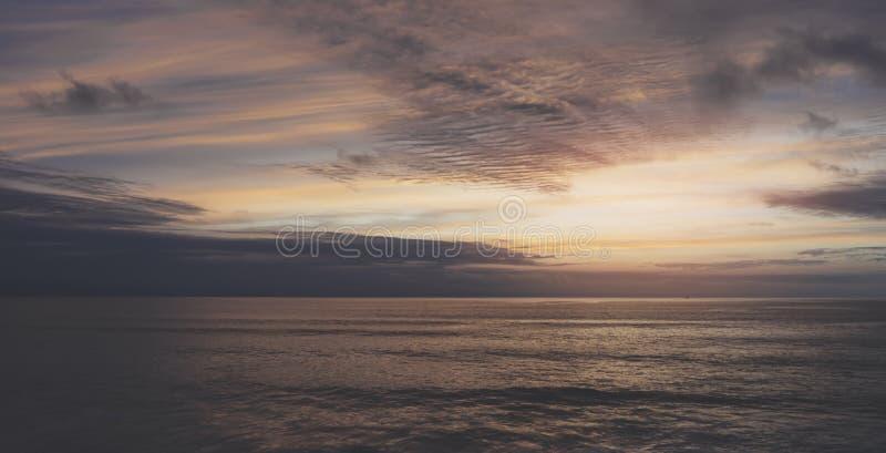 Sunlight sunset on horizon ocean on background seascape rays sunrise. Relax view waves sea on evening sand beach, sun light flare. Nature evening outdoor stock image