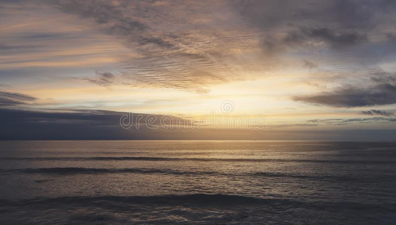 Sunlight sunset on horizon ocean on background seascape rays sunrise. Relax view waves sea on evening sand beach, sun light flare. Nature evening outdoor royalty free stock images
