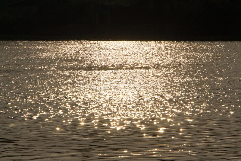 Sunlight from sunsets reflected on the water. Sunlight from sunsets reflected on the water creates a golden shimmering surface stock image