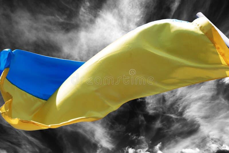Sunlight Ukrainian flag waving in wind on black and white sky stock images