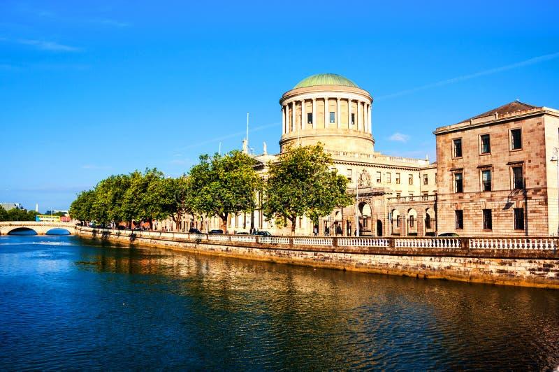 Sunlighted fyra domstolar som bygger i Dublin, Irland med floden Liffey royaltyfri bild