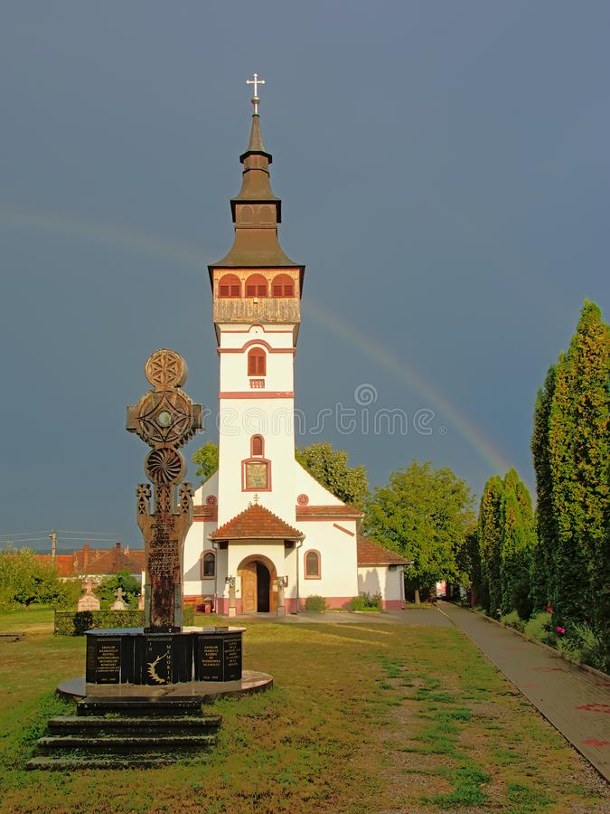 Orthodox assumption church with cross in front in ORastie, Romania. Sunlit Assumption church owith cross in front against a dark sky with rainbow in Orastie stock photo
