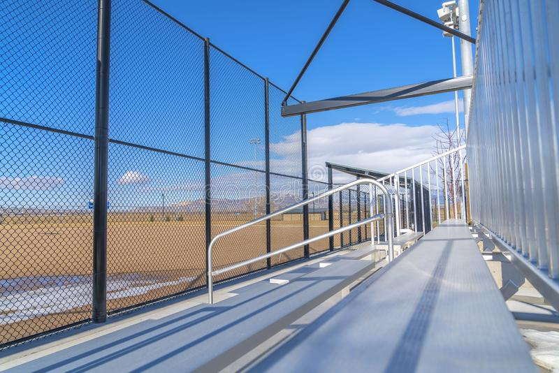 Sunlit bleachers overlooking a vast sports field on the other side of the fence. A snow capped mountain under blue sky can also be viewed from the stands royalty free stock photography