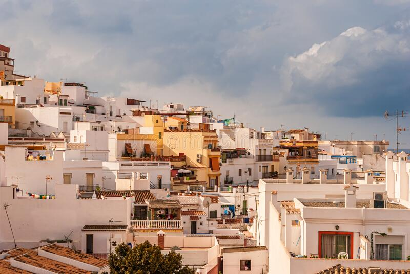 Sunlit houses and apartments in the Costa Tropical town of La Herradura, Granada, Spain. As a dark, cloudy and stormy sky approaches over the skyline royalty free stock photo