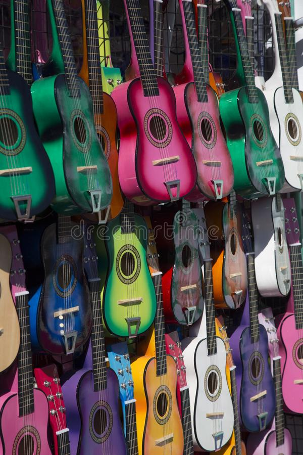 Sunlit, Isolated Angular View of Colorful Small Children`s Guitars Hanging Up - Horizontal Format stock images