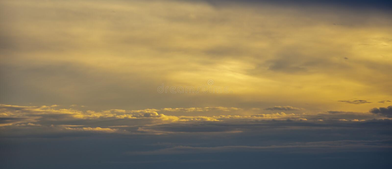 sunlit molnig sky Solnedg?ng arkivbild