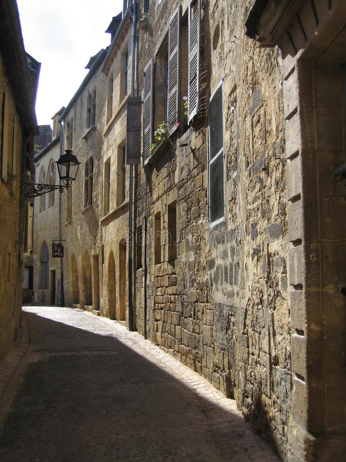 Sunlit narrow street in Sarlat, Dordogne stock images