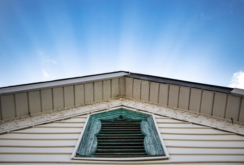 Sunlit rays shining behind peaked roof with rustic blue window stock image