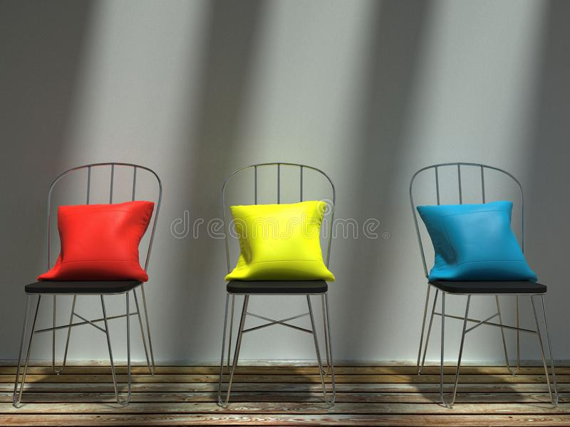 Sunlit red, yellow and blue cushions on metal chairs royalty free stock photography