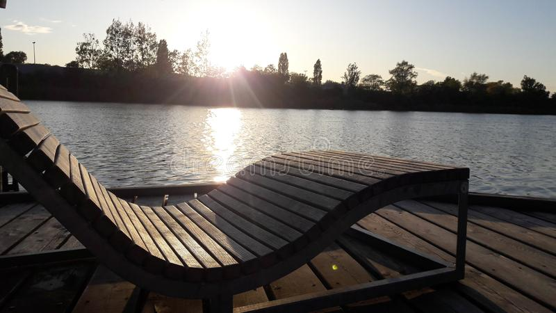 Deck chair on dock at sunset. Empty wooden deckchair on dock along river at sunset royalty free stock photo