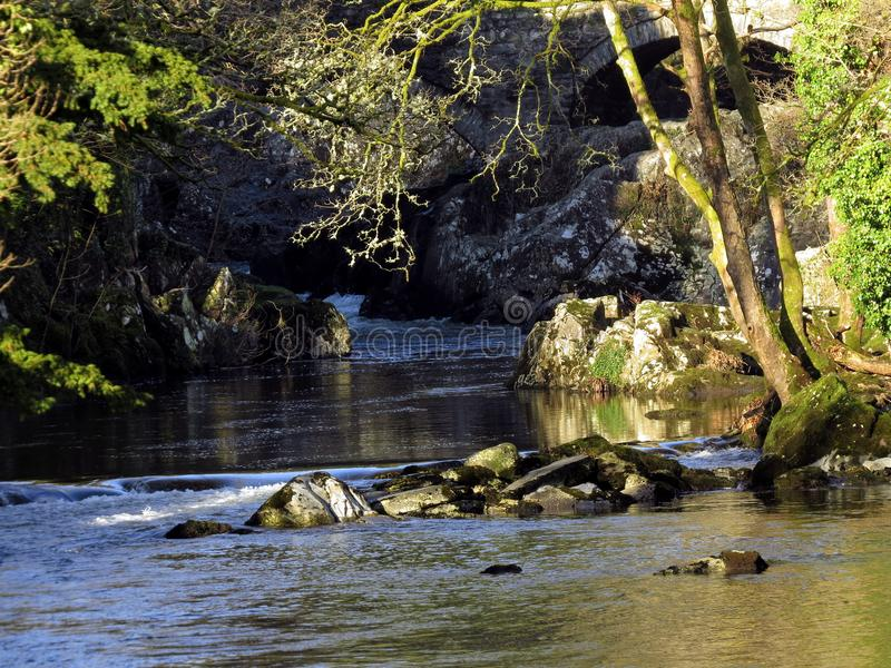 River, sunloit, with rocks small and large royalty free stock photos