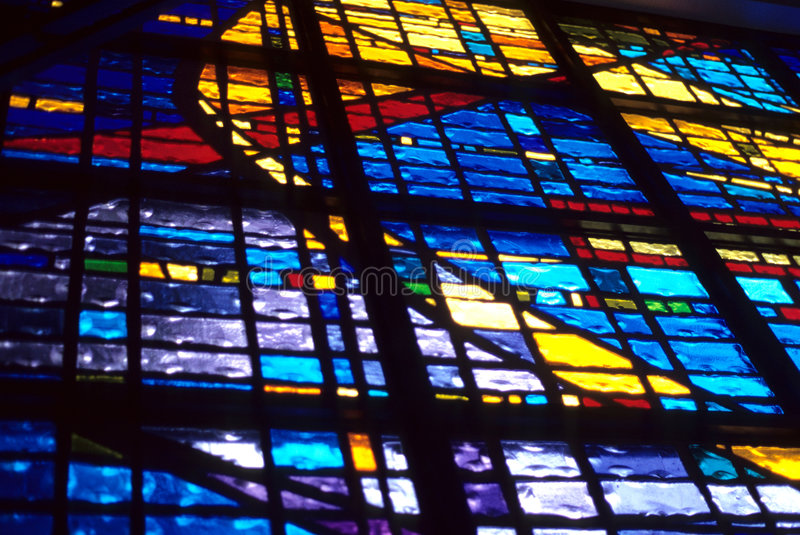 Sunlit Stained Glass. A stained glass window with light streaming through showing all the boldness of the color in the artwork stock photo