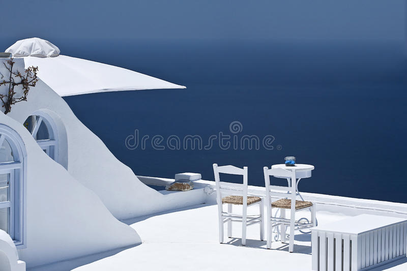 Sunlit terrace. Two white chairs and table on a sunlit terrace. Idyllic view of Mediterranean sea. Space for your text or announcement stock image