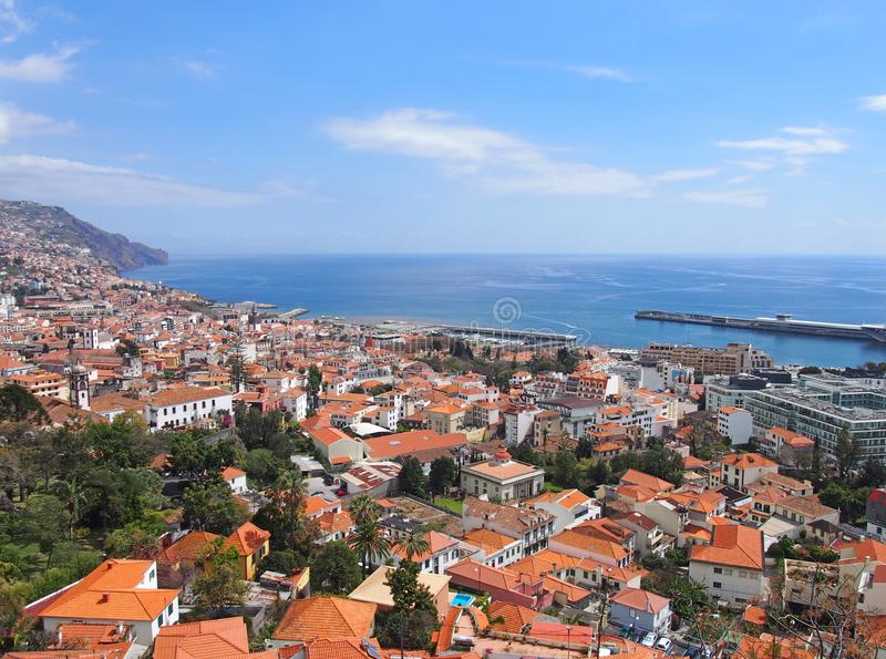 Sunlit view of the city of funchal from above with rooftops and buildings in front of a bright blue sea. A sunlit view of the city of funchal from above with royalty free stock photo