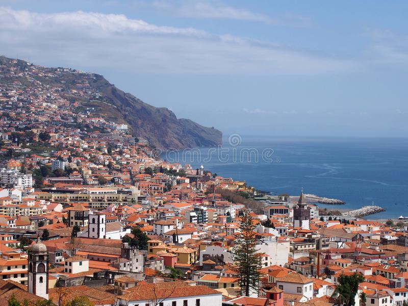Panoramic sunlit view of the city of funchal from above with rooftops and buildings in front of a bright blue sea. A sunlit view of the city of funchal from royalty free stock image