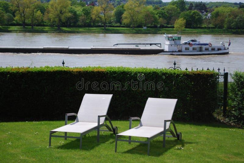Sunlounger en un jardín directo en el río fotografía de archivo