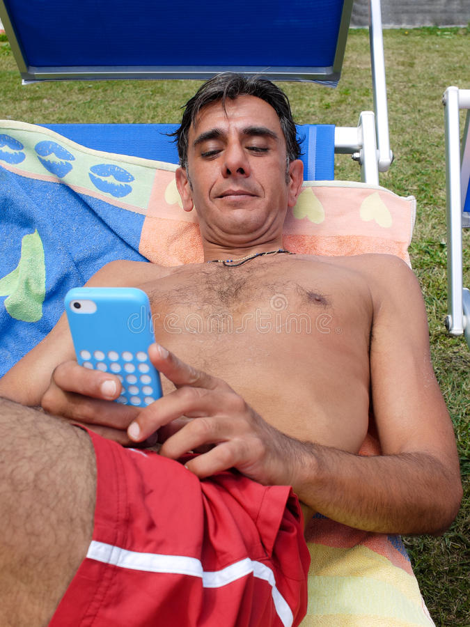 On sunlounger with smartphone stock photo