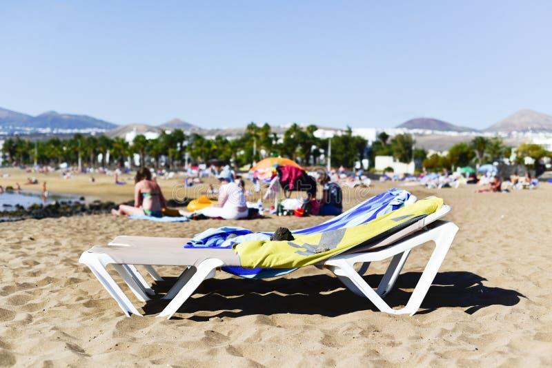 Playa de Matagorda beach in Lanzarote, Spain. Sunloungers and unrecognizable people relaxing at the Playa de Matagorda beach in Puerto del Carmen, Lanzarote, in stock photos