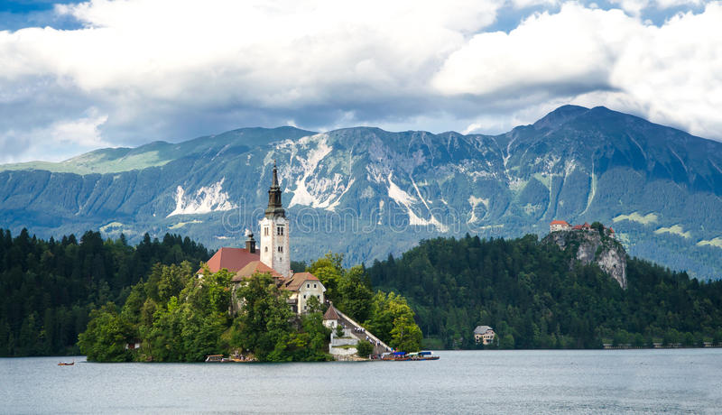 Sunning panoramic view of The island of Bled, Bled castle on cliff, Julian Alps and Church of the Assumption,Bled, Slovenia. Bled, Slovenia- 29 June, 2014 stock image