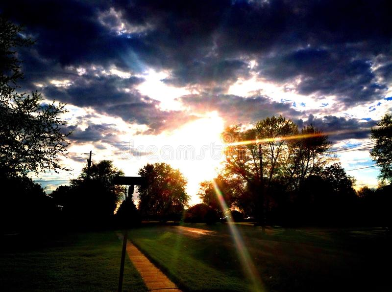 Sunny Afternoon Walk. Sun shining through dark lined clouds in the evening stock photo