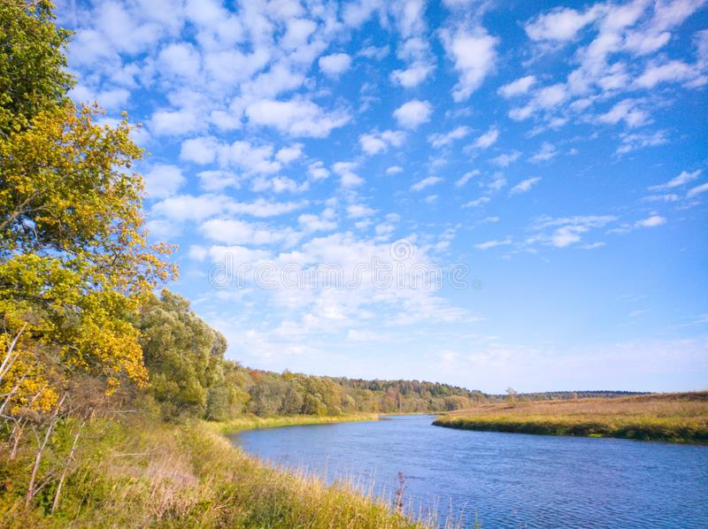 Sunny autumn day by the river bend in the countryside. Sunny autumn day river countryside rural  bend blue sky bright september october reflection foliage stock images