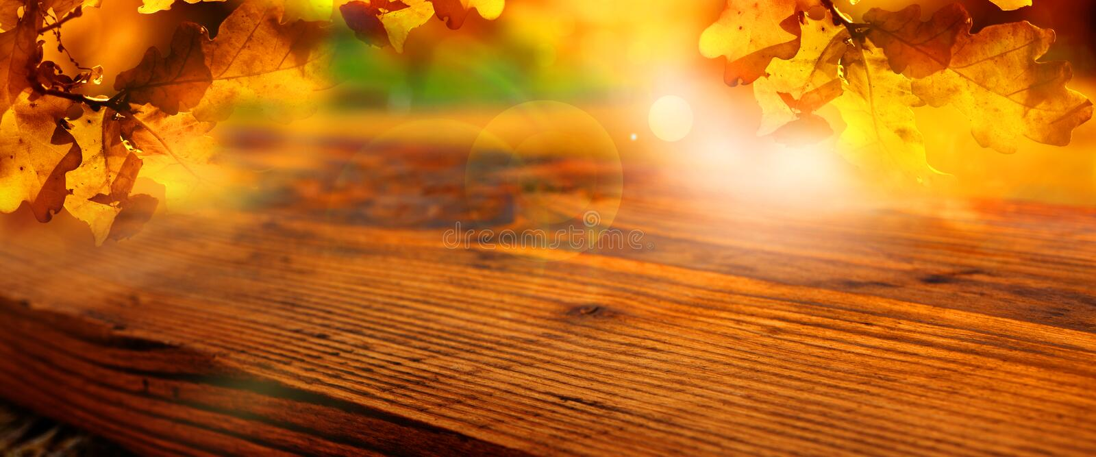Sunny autumn leaves with wooden table stock photo