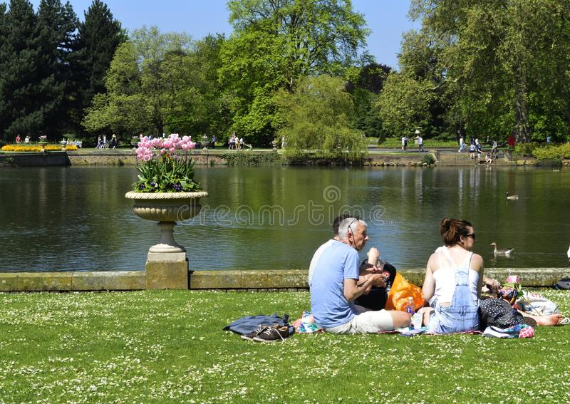 Family Having a Picnic beside Kew Gardens Lake in London Uk. A sunny bank holiday and a family sitting by kew gardens lake having a picnic lunch royalty free stock photos