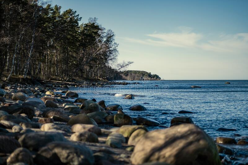 sunny beach with blue water and large rocks in the sand royalty free stock photos