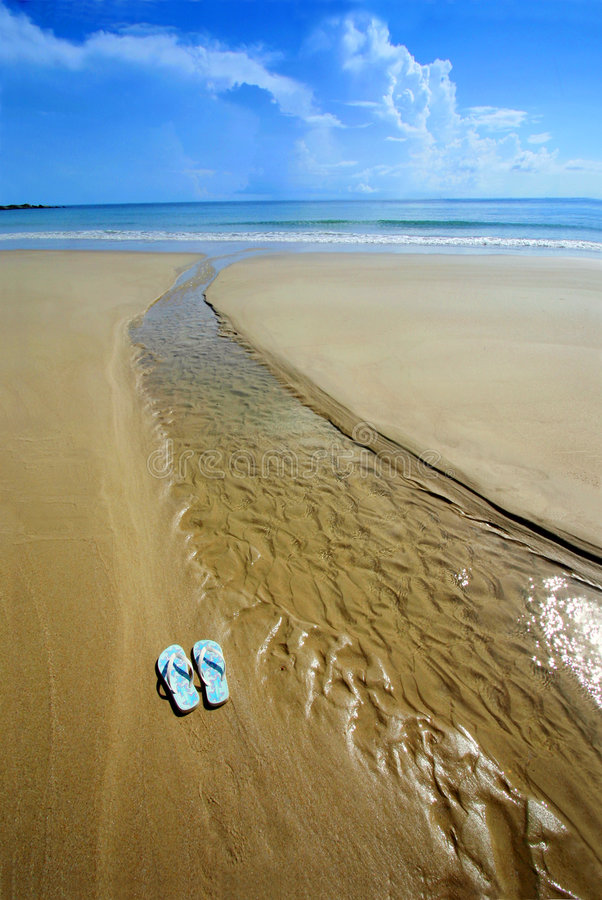 Sunny beach, flip flops on sand. Barefoot on the sand with blue sea ahead - A pair of blue sandals flip flops next to a rivulet of sea water on a bright sunny stock images