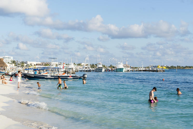 Sunny beach in Isla Mujeres, Mexico. Tourists enjoy the sunny weather and relaxing on the beach on 21 January 2015 in Isla Mujeres, Mexico. The island is located stock photo