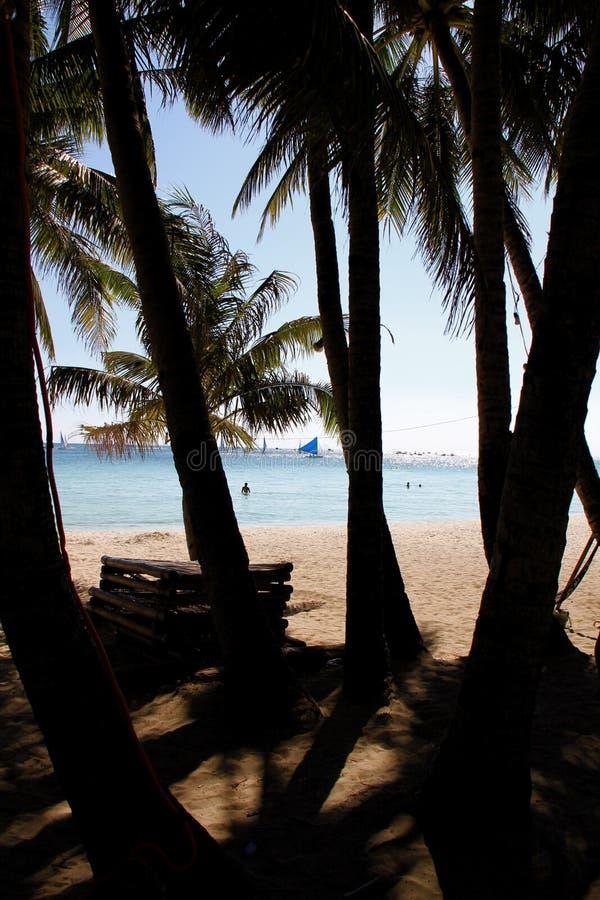 Sunny Beach und Ozean mit Segelboot von einer kühlen Schattenstelle stockfoto