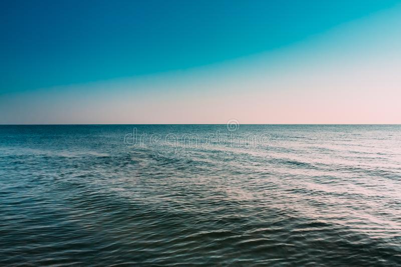 Sunny Blue Clear Sky Over Calm Water Of Sea Or Ocean. Natural Seascape. Background With Gently Blue Colors stock image