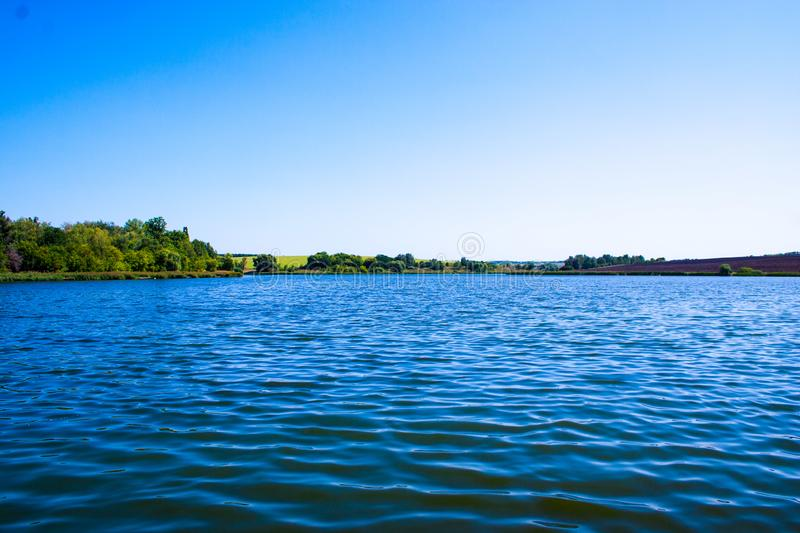 August calm lake. Sunny cloudless day in August, a calm lake, a plowed field, green trees and reeds on the opposite shore of the lake royalty free stock photography